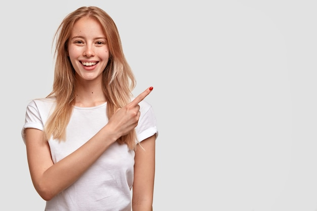 Mulher europeia alegre com sorriso largo, olhar atraente, aponta à parte, vestida com camiseta branca casual, mostra algo agradável, anuncia novo item na loja, copie espaço para seu texto ou promoção