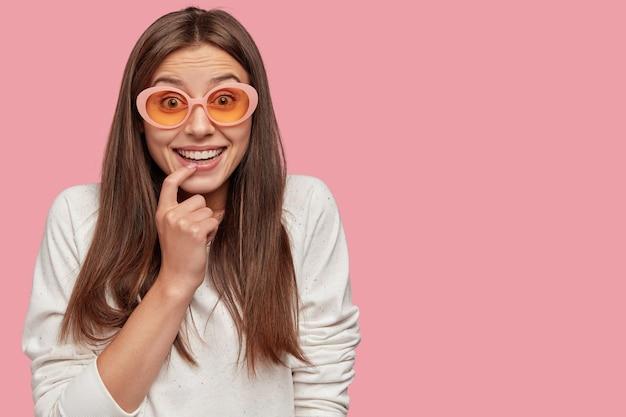 Mulher europeia alegre e positiva tem um sorriso dentuço, mantém o dedo indicador perto dos lábios, satisfeita com as boas notícias, ri com um amigo