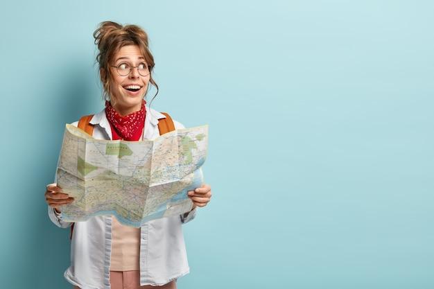Mulher europeia alegre faz viagem interessante, olha para o lado, segura mapa, verifica rota ou localização, viaja na cidade turística