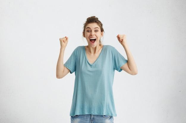 Mulher europeia animada e alegre gritando de alegria e empolgação, cerrando os punhos