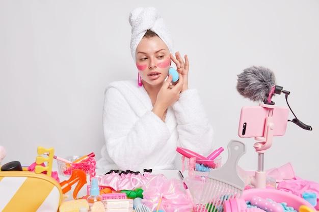 Mulher europeia aplica base com esponja protetora sob os olhos