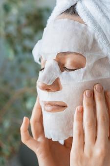 Mulher europeia aplica máscara hidratante de pano branco no rosto cuidados com a pele facial e tratamentos de spa