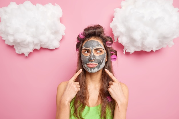 Mulher europeia aponta para o rosto demonstra produto de beleza aplicado no rosto faz corte de cabelo encaracolado concentrado ao lado isolado sobre parede rosada