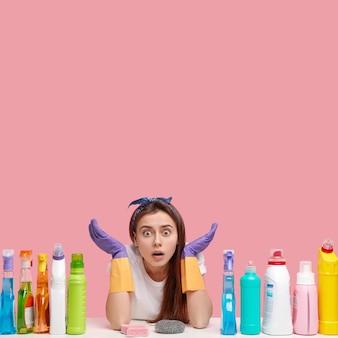 Mulher europeia atordoada e emocional em luvas de borracha posa à mesa com materiais de limpeza, espalha as mãos em perplexidade, prepara detergentes para a limpeza, copie o espaço para cima. arrumando o conceito.