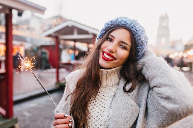 Mulher europeia atraente com casaco cinza, comemorando o ano novo na rua, segurando a luz de bengala. retrato ao ar livre de uma menina morena feliz com lábios vermelhos, posando com diamante no inverno.