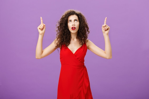 Mulher européia atraente focada perplexa com penteado encaracolado em vestido de noite vermelho com a boca aberta, levantando os braços, olhando e apontando para cima pensativa e curiosa sendo incomodada sobre o fundo roxo.