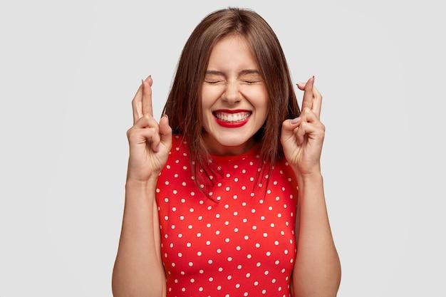 Mulher européia atraente satisfeita quer ganhar, levanta as mãos com os dedos cruzados, espera o resultado da loteria, fecha os olhos