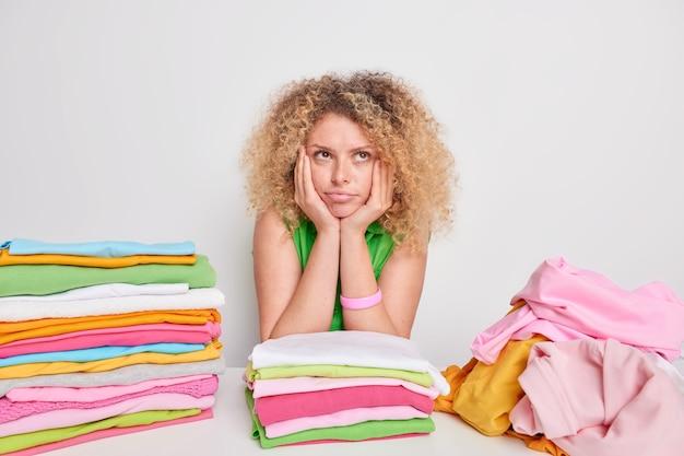 Mulher européia bem atenciosa com cabelo encaracolado mantém as mãos embaixo do queixo, expressão pensativa, dobra a roupa, faz tarefas domésticas isoladas sobre o branco