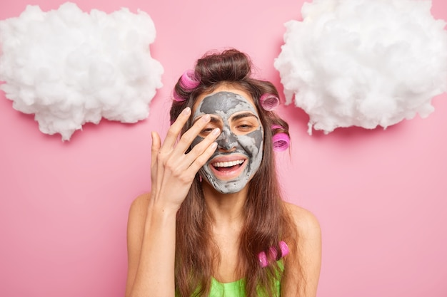 Mulher européia bonita e alegre aplica máscara de argila no rosto, rejuvenesce a pele, sorri, poses ampla, interior, contra parede rosa, faz penteado com rolos de cabelo, passa tempo cuidando de si mesma