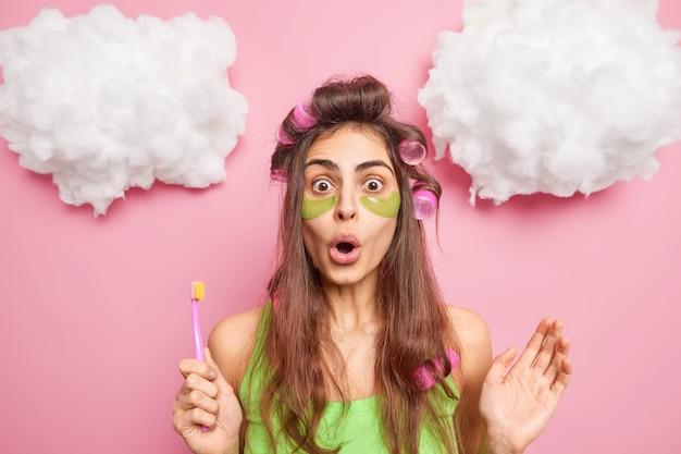 Mulher européia chocada e surpresa com a rotina matinal se torna linda aplica manchas de colágeno verde sob os olhos, escova os dentes regularmente usa bobes de cabelo para fazer um penteado perfeito