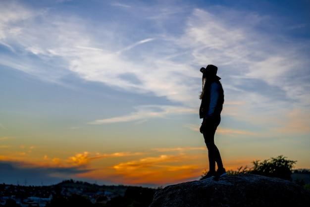 Mulher europeia com chapéu de cowboy de pé em uma pedra e olhando o pôr do sol