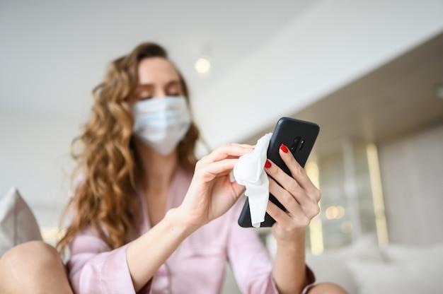 Mulher européia com máscara facial, limpando o telefone com desinfetante para as mãos, usando algodão com álcool para limpar e evitar contaminação com o vírus corona. limpeza de celular para eliminar germes, covid-19.