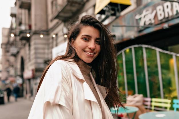Mulher europeia com um sorriso feliz e cabelos escuros sorrindo para a câmera e caminhando com emoções felizes