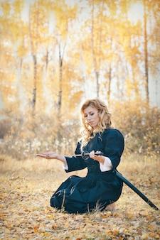 Mulher europeia com uma katana de quimono. a garota treina artes marciais. uma mulher na floresta de outono. um guerreiro com uma arma fria nas mãos