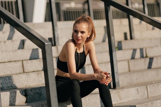 Mulher europeia com uniforme de esporte sentada na escada e se preparando para um treinamento externo