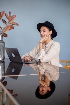 Mulher europeia com vestido e chapéu clássico trabalha em casa na cozinha