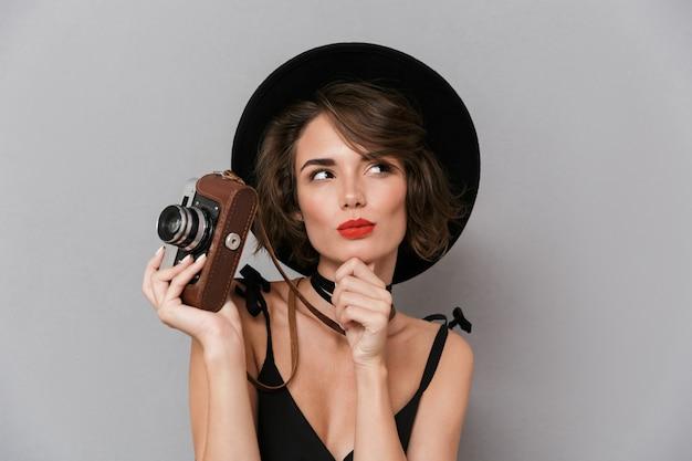 Mulher europeia com vestido preto e chapéu fotografando na câmera retro, isolada sobre uma parede cinza