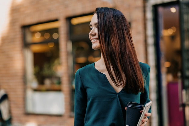 Mulher europeia confiante em vestido escuro, olhando para longe