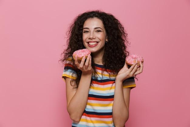 Mulher européia de 20 anos com cabelo encaracolado brincando e comendo rosquinhas isoladas em rosa