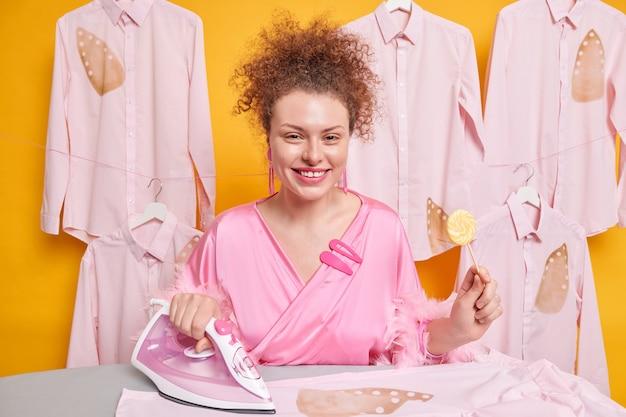 Mulher europeia de cabelo encaracolado positiva usa ferro a vapor para acariciar roupas segura pirulito usa roupão rosa isolado sobre a parede amarela na lavanderia. conceito de engomar e trabalhos domésticos