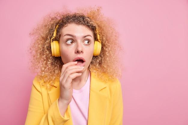 Mulher europeia de cabelos cacheados assustada usa fones de ouvido para ouvir música desviando o olhar ouve faixa de áudio vestida elegantemente isolada sobre fundo rosa com espaço de cópia em branco de distância