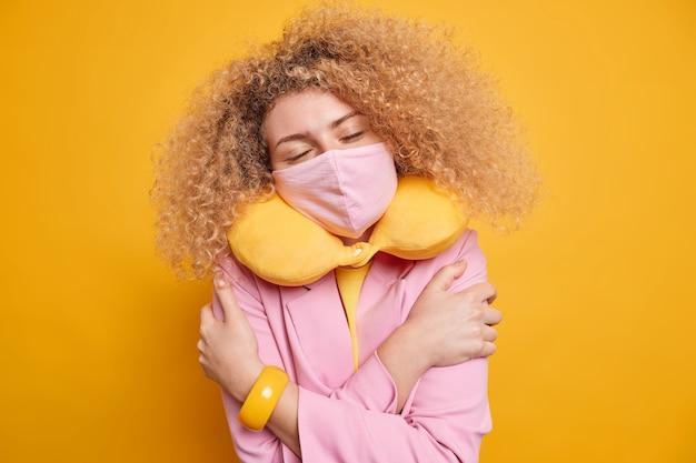 Mulher européia de cabelos cacheados satisfeita se abraça, sente conforto, mantém os olhos fechados, usa máscara protetora contra coronavírus travesseiro macio ao redor do pescoço poses internas contra parede amarela