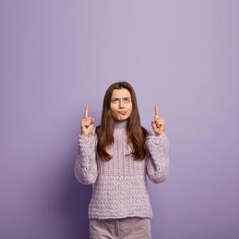 Mulher europeia de cabelos escuros chateada franze os lábios, franze o rosto, aponta os dois dedos da frente, usa um macacão de malha roxa, mostra algo acima, insatisfeita com o item acima. olhe para cima. tiro.
