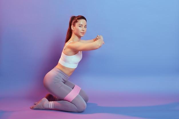 Mulher europeia de cabelos escuros desportiva, vestindo blusa e leggins, sentada de joelhos no chão e fazendo exercícios de esporte com resistência para a parte interna das coxas, olha para a câmera, mãos na frente do peito.