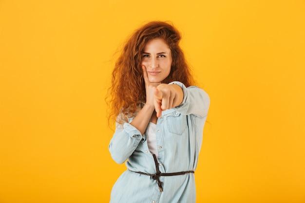 Mulher europeia de conteúdo apontando o dedo para você, isolado sobre fundo amarelo