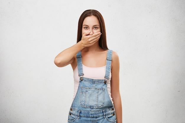 Mulher européia de macacão jeans, cobrindo a boca com a mão, tentando manter o silêncio e não contar segredo. mulher atraente, mantendo segredo contado por sua melhor amiga. conceito de sigilo e conspiração
