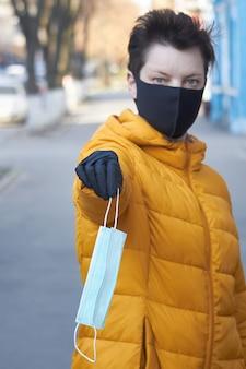Mulher européia de meia idade em máscara e luvas pretas protetoras mantém uma máscara protetora durante a epidemia de coronavírus covid-19