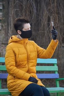 Mulher européia de meia idade em máscara e luvas pretas protetoras tira selfie no smartphone do lado de fora durante a epidemia de coronavírus covid-19