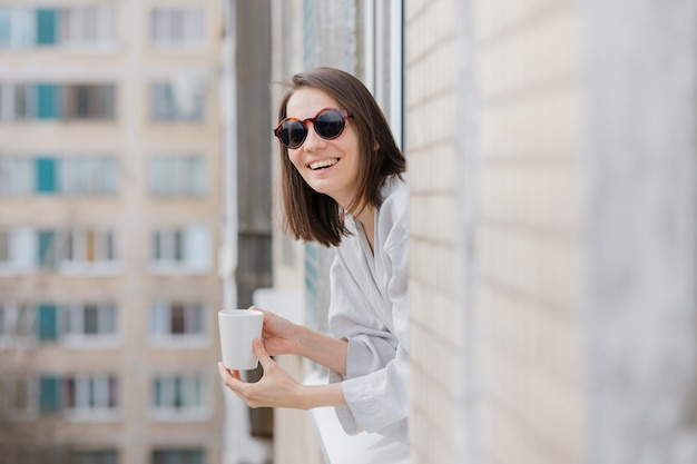 Mulher europeia de óculos escuros e com uma caneca de café ou chá olhando pela janela