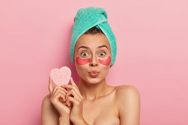 Mulher européia de olhos verdes de aparência agradável usa adesivos de hidrogel sob os olhos para acalmar a pele delicada, reduz as bolsas nos olhos após o trabalho cansativo, tem os lábios dobrados, segura uma esponja cosmética para maquiagem.