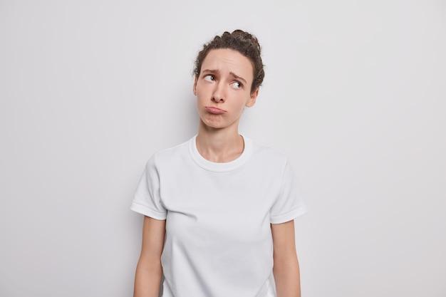 Mulher européia deprimida e triste franze os lábios e tem uma expressão sombria no rosto vestida com uma camiseta casual básica inclina a cabeça em poses contra a parede cinza