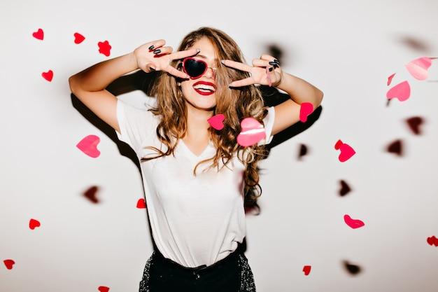 Mulher européia deslumbrante em óculos de sol vermelhos se divertindo em casa, festa