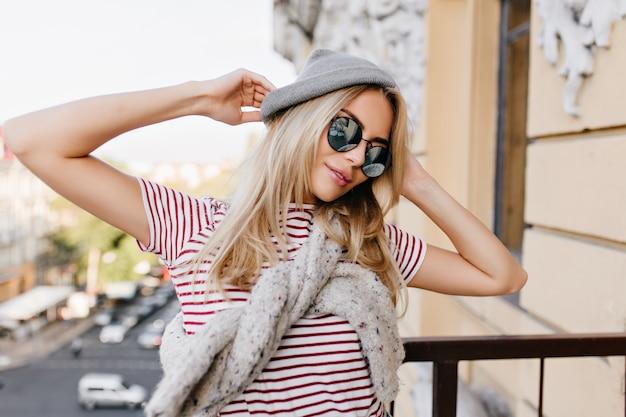 Mulher europeia deslumbrante em óculos elegantes posando com as mãos ao alto durante a sessão de fotos no fundo da cidade