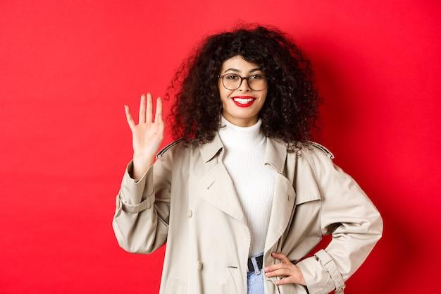 Mulher europeia elegante de óculos e sobretudo, dispensando a mão e sorrindo, dizendo olá, cumprimentando alguém, de pé sobre fundo vermelho.