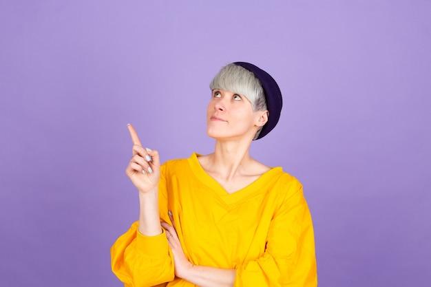 Mulher europeia elegante na parede roxa