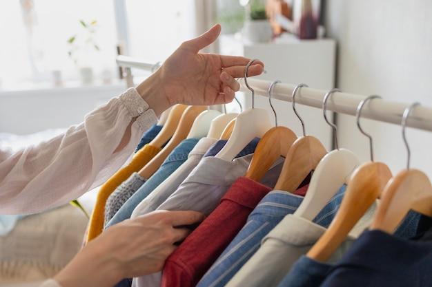 Mulher europeia em casa no guarda-roupa seleciona roupas para uma festa ou festa de aniversário escolhendo roupas