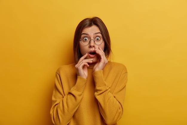 Mulher europeia em pânico e chocada sente-se desapontada e impressionada, ouve algo inacreditável, usa óculos redondos e suéter casual, isolada sobre a parede amarela, fica muda.