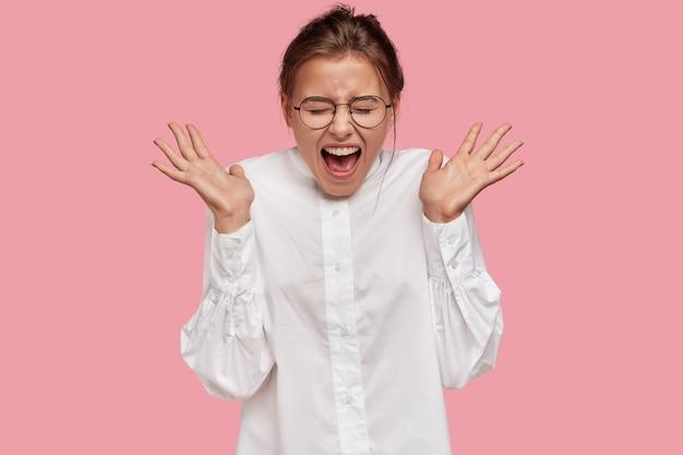 Mulher européia emocionada e animada abre as palmas das mãos e exclama bem alto