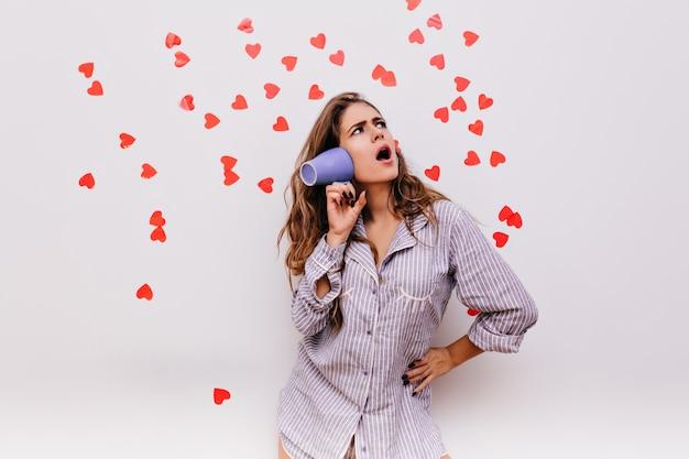 Mulher europeia emocional de pijama azul brincando no estúdio