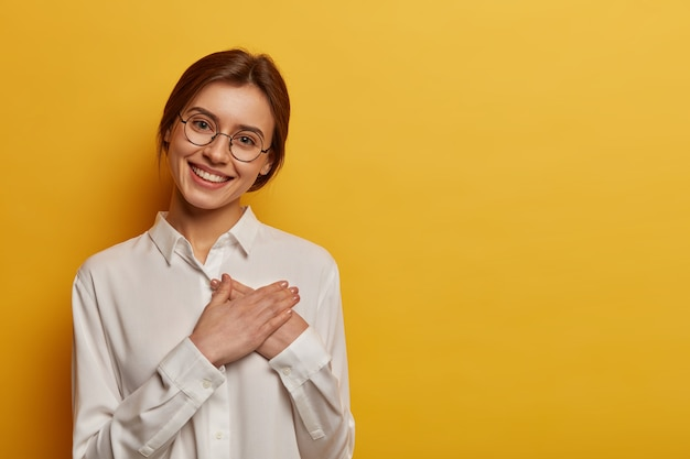 Mulher europeia encantadora e positiva aperta as mãos contra o peito, expressa gratidão pelo presente, agradece a ajuda, usa óculos redondos e camisa branca