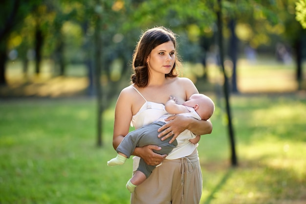 Mulher européia está amamentando bebê ao ar livre em público