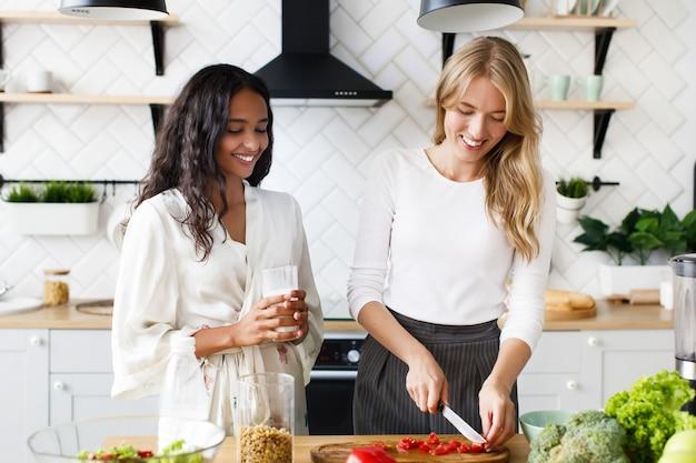 Mulher europeia está cortando um tomate e mulher africana está bebendo leite, eles sorriem