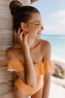 Mulher europeia fascinante com pele bronzeada expressando felicidade pela manhã em lugar exótico. foto ao ar livre da adorável garota caucasiana em trajes de banho laranja na moda sorrindo.