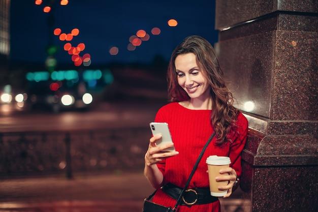 Mulher europeia feliz usar smartphone na noite