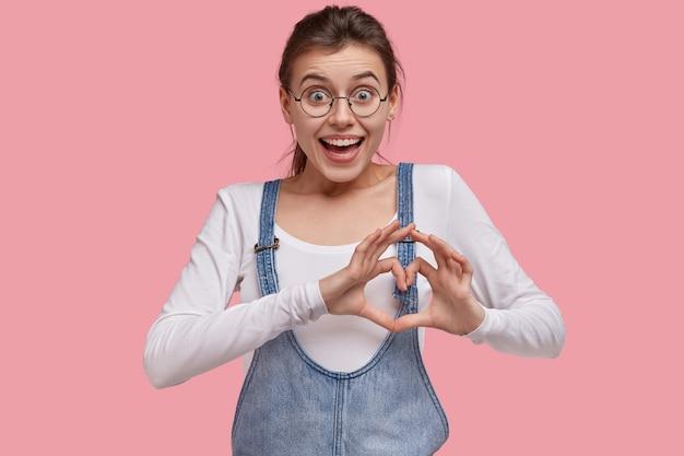 Mulher européia fofa e positiva faz gestos de coração com as duas mãos, expressa amor ao namorado e diz
