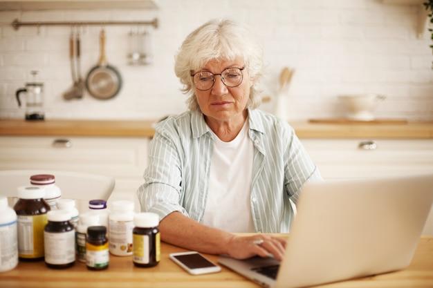Mulher européia idosa aposentada descontente com óculos redondos, sentada na cozinha, olhando para frascos de suplemento alimentar com desprezo, digitando crítica negativa irritada no site usando um laptop
